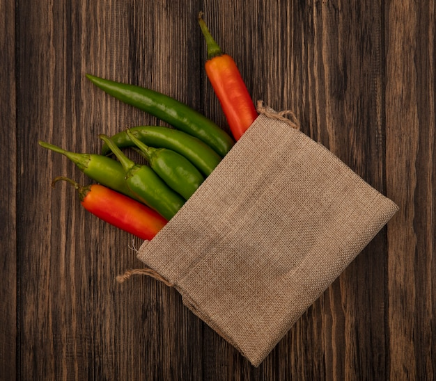 Bovenaanzicht van kleurrijke en verse paprika's op een jutezak op een houten oppervlak