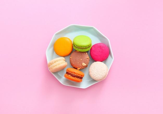 Bovenaanzicht van kleurrijke franse bitterkoekjes op blauw bord op roze achtergrond. amandelkoekjes. valentijnsdag zoete cadeau concept, vakantie, feest.