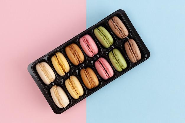 Bovenaanzicht van kleurrijke franse macarons in pakket op roze-blauwe achtergrond