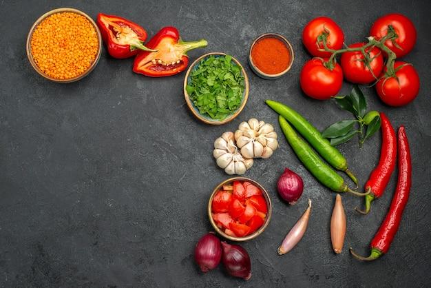 Bovenaanzicht van kleurrijke groenten linze in kom naast de kleurrijke groenten en kruiden