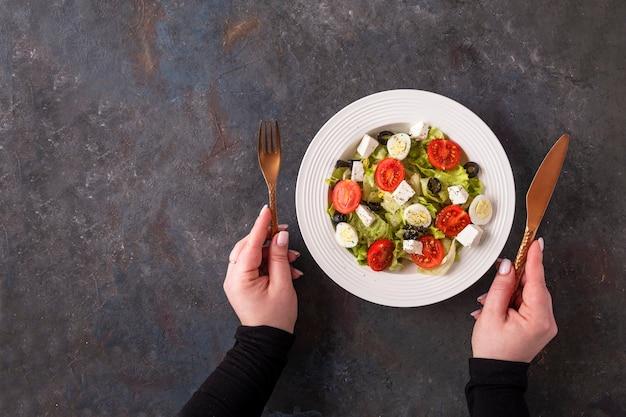 Bovenaanzicht van kleurrijke groenten met kwarteleitjes en kaas op een bord. vrouwelijke handen houdt mes en vork. kopieer ruimte