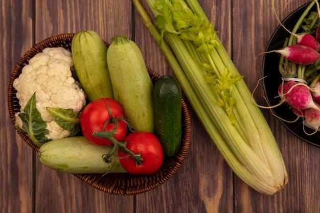 Bovenaanzicht van kleurrijke groenten zoals tomaten, courgette, komkommer en bloemkool op een emmer met radijs op een kom met selderij geïsoleerd op een houten muur