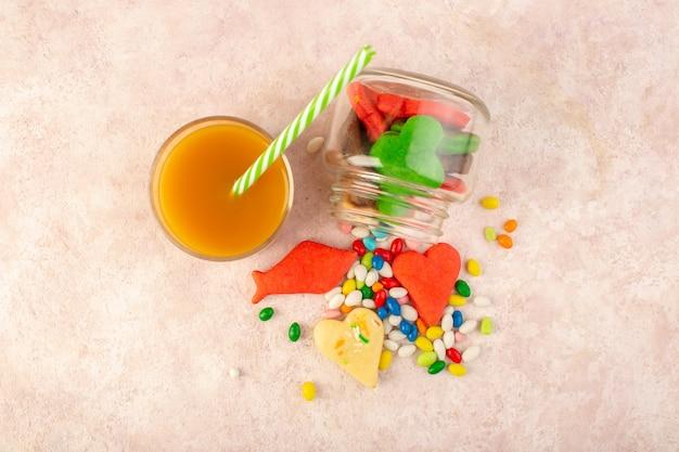 Bovenaanzicht van kleurrijke heerlijke koekjes verschillend gevormd binnen kan met snoepjes en vers perziksap op het roze oppervlak