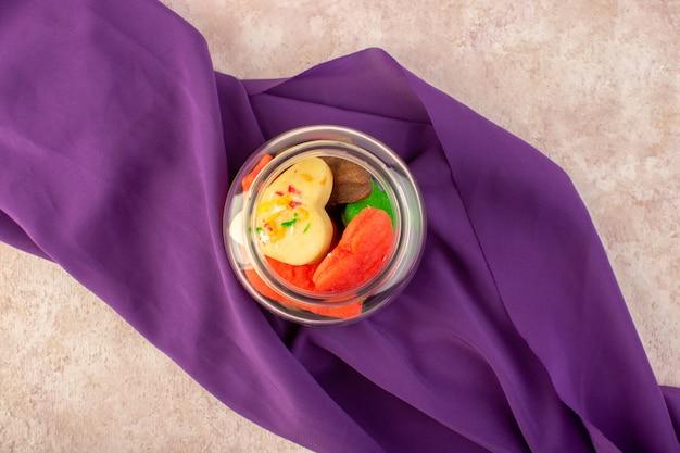Bovenaanzicht van kleurrijke heerlijke koekjes verschillend gevormd binnen kan op het paarse weefsel en roze oppervlak