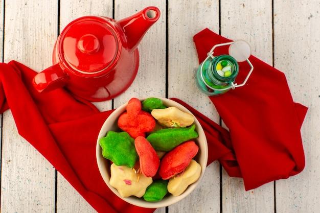 Bovenaanzicht van kleurrijke heerlijke koekjes verschillend gevormd binnen plaat met rode ketel en snoepjes