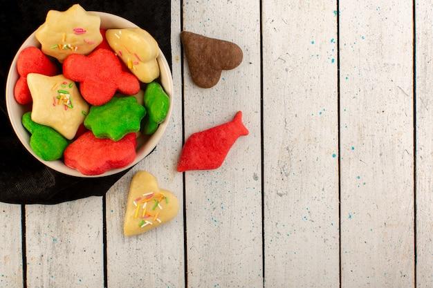 Bovenaanzicht van kleurrijke heerlijke koekjes verschillend gevormd binnen plaat op het grijze koekje zoete suiker