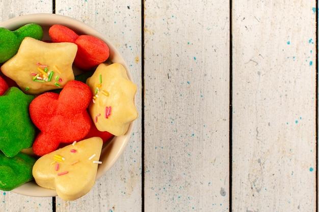 Bovenaanzicht van kleurrijke heerlijke koekjes verschillend gevormd binnen ronde plaat op het grijze oppervlak