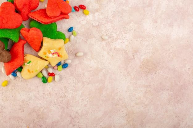 Bovenaanzicht van kleurrijke heerlijke koekjes verschillend gevormd met snoepjes op het roze oppervlak
