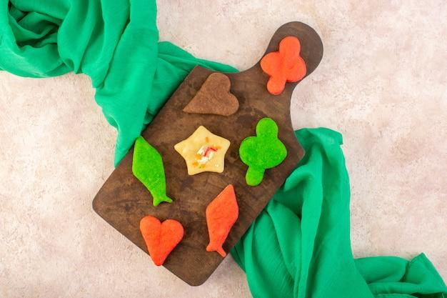Bovenaanzicht van kleurrijke heerlijke verschillende koekjes gevormd op het bruine houten bureau