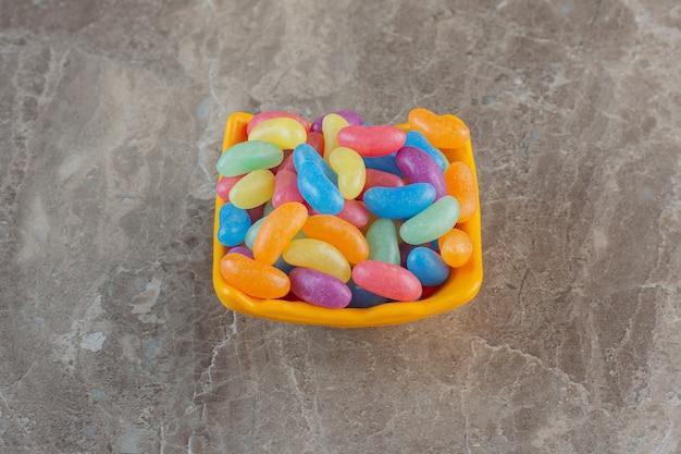 Bovenaanzicht van kleurrijke jellybeans in oranje kom over grijs oppervlak.