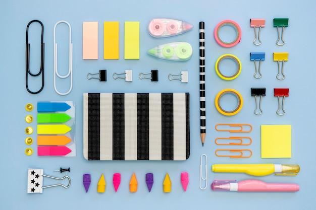 Bovenaanzicht van kleurrijke kantoorbenodigdheden met paperclips en tape