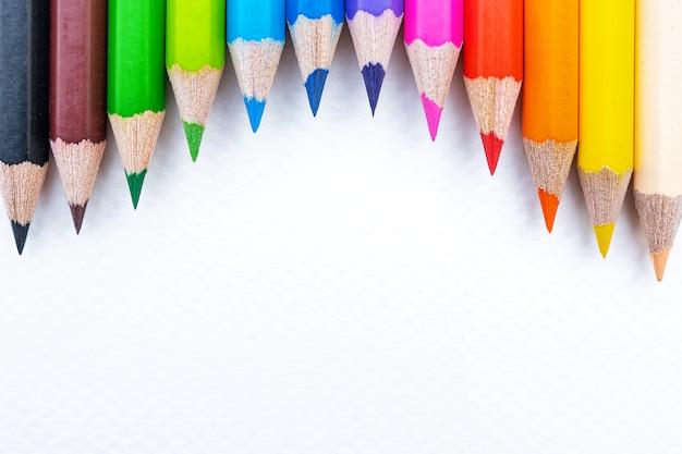 Bovenaanzicht van kleurrijke kleurpotloden in bereik geïsoleerd op wit papier