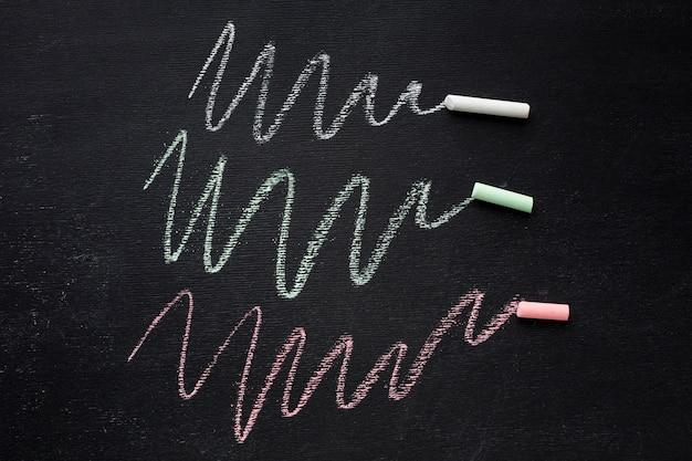 Bovenaanzicht van kleurrijke krijt op schoolbord