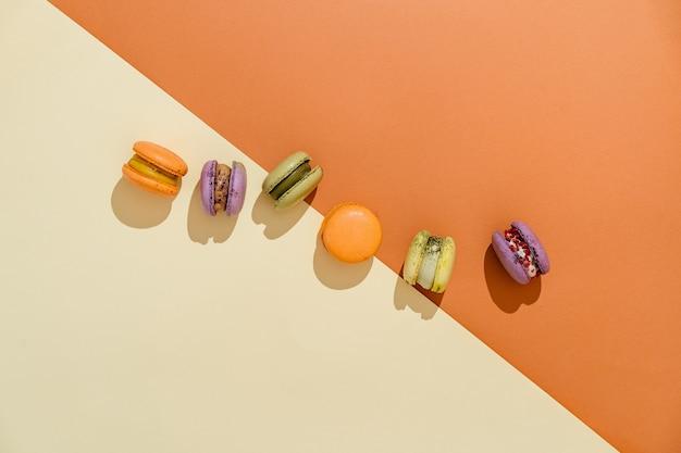 Bovenaanzicht van kleurrijke macaron of macaroon op oranje beige achtergrond. selectieve aandacht. plat leggen