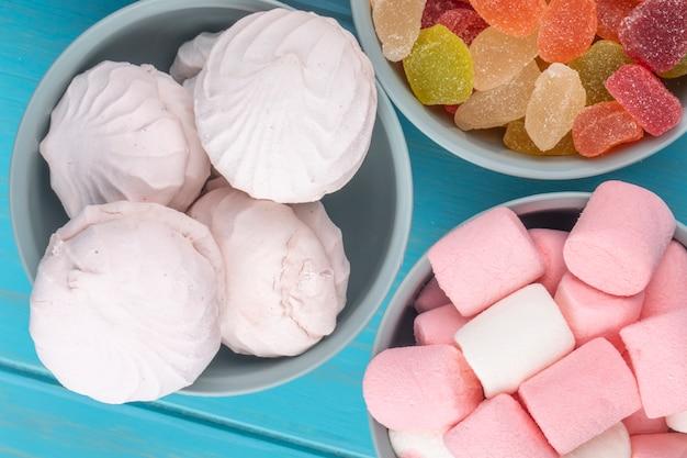 Bovenaanzicht van kleurrijke marmelade snoepjes met witte zefier en marshmallows in kommen op blauw