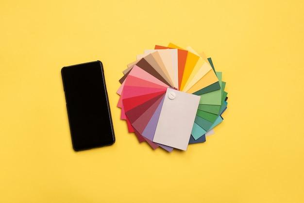 Bovenaanzicht van kleurrijke monsters en smartphone met leeg scherm op gele achtergrond.
