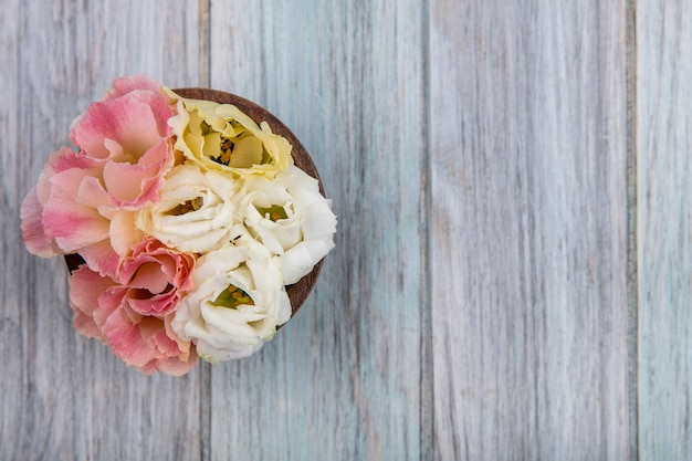 Bovenaanzicht van kleurrijke mooie bloemen op een houten kom op een grijze houten achtergrond met kopie ruimte