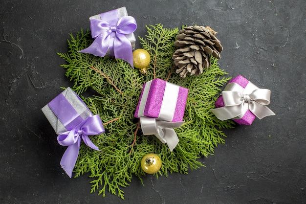 Bovenaanzicht van kleurrijke nieuwjaarsgeschenken decoratie accessoire en conifer kegel op donkere achtergrond