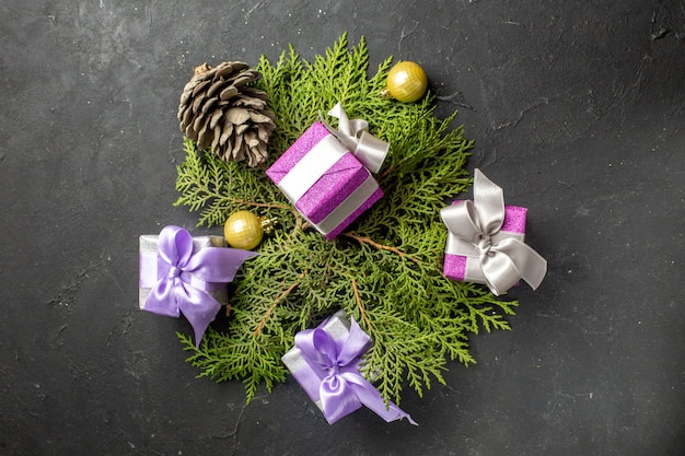 Bovenaanzicht van kleurrijke nieuwjaarsgeschenken decoratie accessoire en conifer kegel op donkere tafel