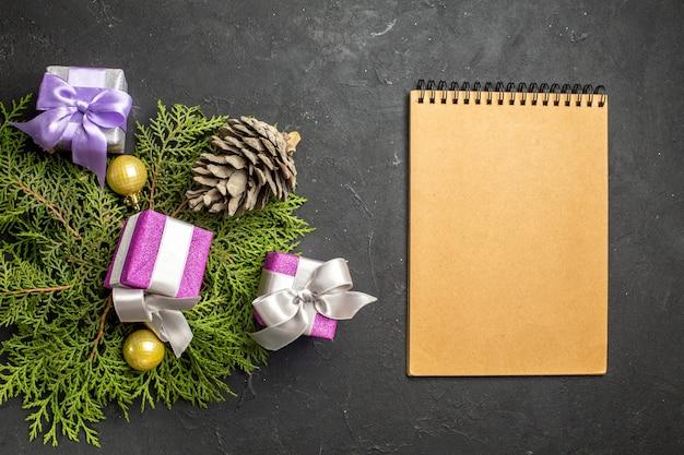 Bovenaanzicht van kleurrijke nieuwjaarsgeschenken decoratie-accessoire en coniferenkegel naast notebook op donkere achtergrond
