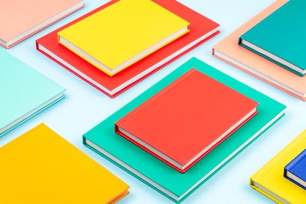 Bovenaanzicht van kleurrijke notitieboekjes over de blauwe pastel muur. moderne abstracte werkruimte, studies, bureauconcept