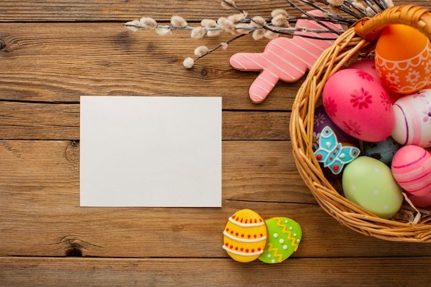 Bovenaanzicht van kleurrijke paaseieren in mand met konijntje en papier