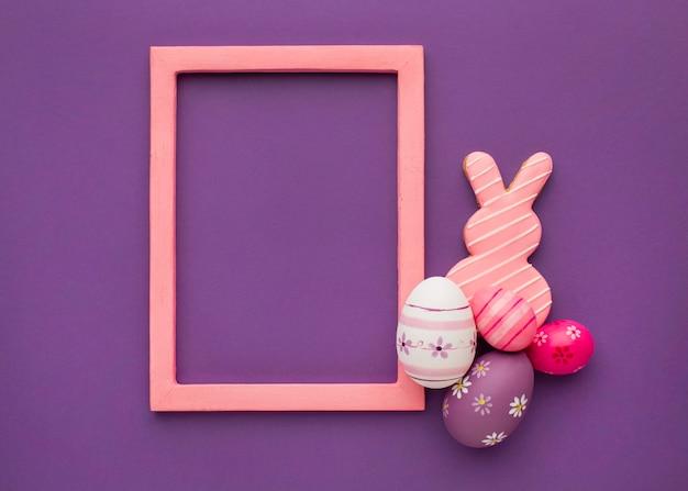 Bovenaanzicht van kleurrijke paaseieren met konijntje en frame