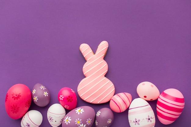 Bovenaanzicht van kleurrijke paaseieren met kopie ruimte en konijntje