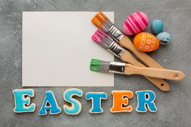 Bovenaanzicht van kleurrijke paaseieren met penselen en papier