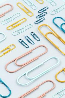Bovenaanzicht van kleurrijke paperclips over de pastelkleurige muur. modern abstract concept van werkruimte, studies, bureau