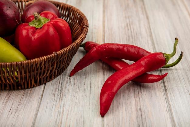 Bovenaanzicht van kleurrijke paprika op een emmer met chilipepers geïsoleerd op een grijze houten achtergrond