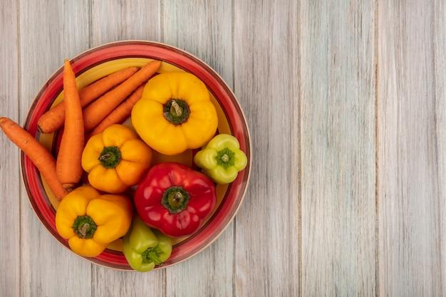 Bovenaanzicht van kleurrijke paprika's op een bord met wortelen op een grijze houten ondergrond met kopie ruimte