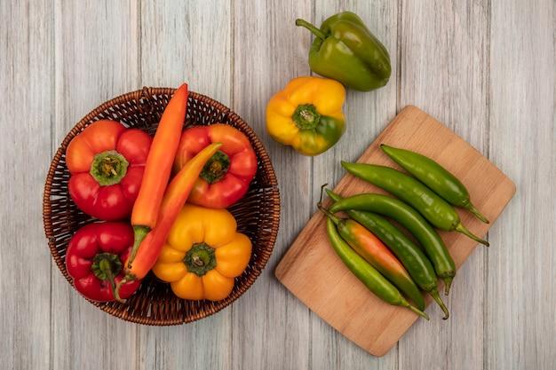 Bovenaanzicht van kleurrijke paprika's op een emmer met lange vorm paprika's op een houten keukenbord op een grijze houten achtergrond