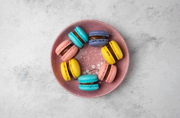 Bovenaanzicht van kleurrijke pastel macarons op witte achtergrond.