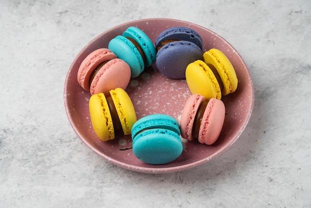 Bovenaanzicht van kleurrijke pastel macarons op witte ondergrond.