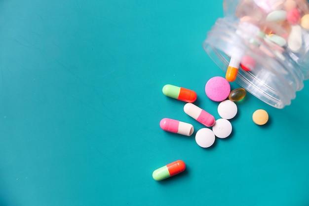 Bovenaanzicht van kleurrijke pillen morsen op groene achtergrond
