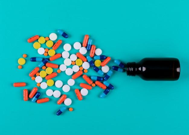 Bovenaanzicht van kleurrijke pillen uit fles