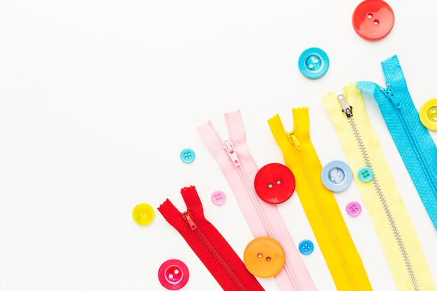 Bovenaanzicht van kleurrijke ritsen en knop met kopie ruimte