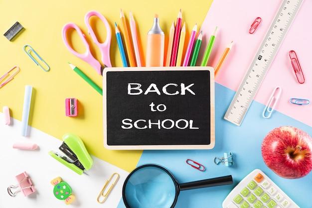 Bovenaanzicht van kleurrijke schoolbenodigdheden op pastel papier. plat liggen.