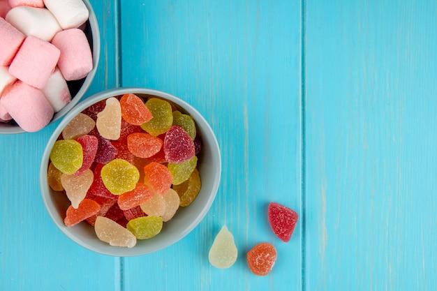 Bovenaanzicht van kleurrijke smakelijke marmelade snoepjes en marshmallows in kommen op blauw