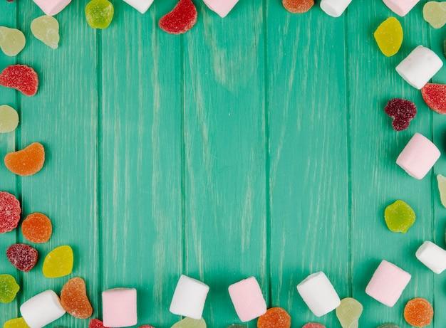 Bovenaanzicht van kleurrijke smakelijke marmelade snoepjes en marshmallows met kopie ruimte op groen