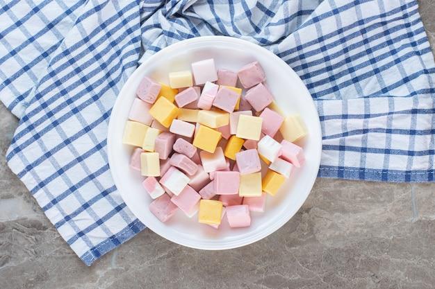 Bovenaanzicht van kleurrijke snoepjes in kubieke vorm. roze wit en geel.