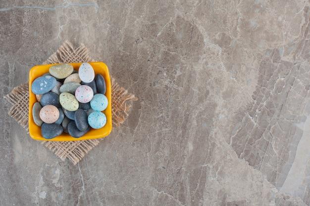 Bovenaanzicht van kleurrijke stenen snoepjes in oranje kom over grijze achtergrond.