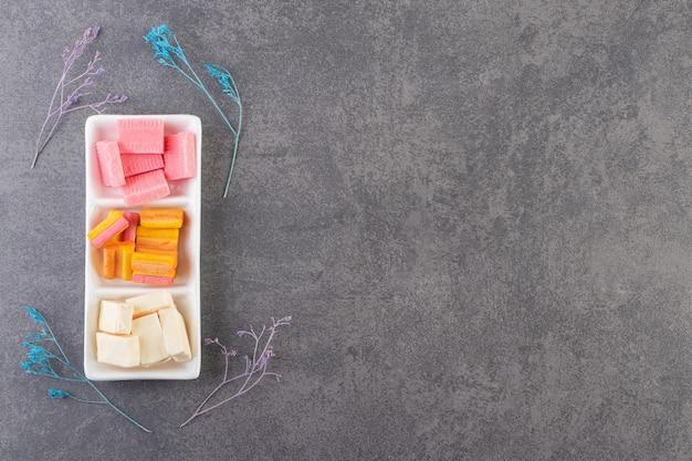 Bovenaanzicht van kleurrijke tandvlees op witte plaat op grijze ondergrond