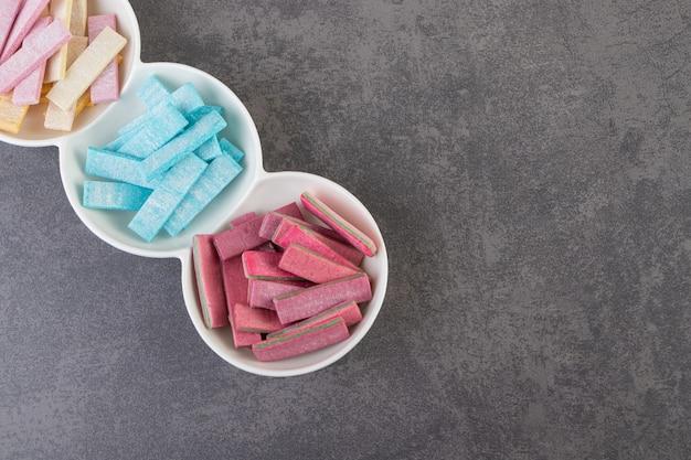 Bovenaanzicht van kleurrijke tandvlees op witte plaat over grijze achtergrond.