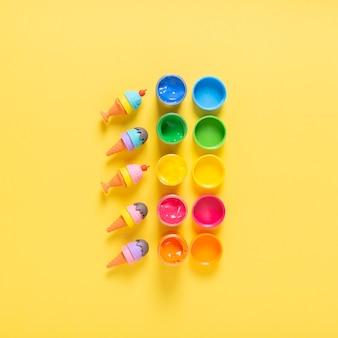 Bovenaanzicht van kleurrijke verf op gele achtergrond
