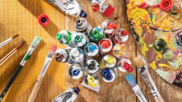 Bovenaanzicht van kleurrijke verftubes met penselen