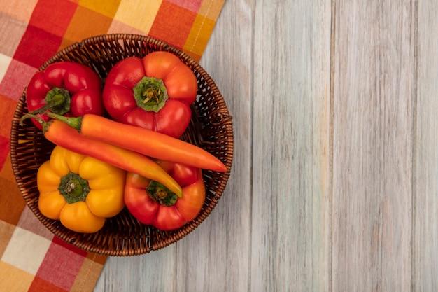 Bovenaanzicht van kleurrijke zoet geproefd paprika's op een emmer op een gecontroleerde doek op een grijze houten ondergrond met kopie ruimte