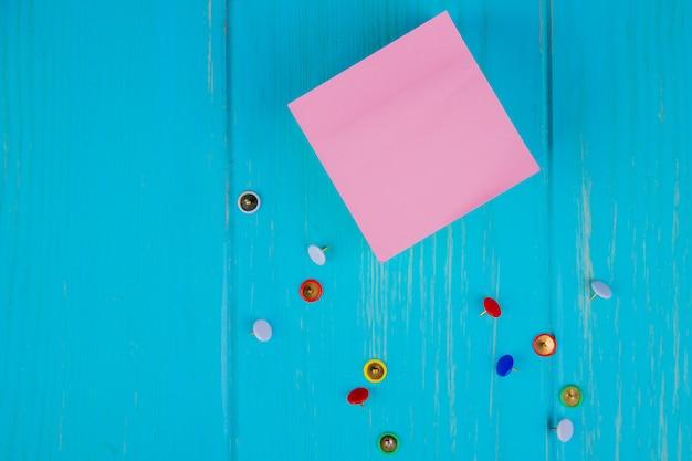 Bovenaanzicht van kleverige memo notitie en kleine pin clips op blauw oppervlak met kopie ruimte