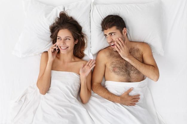 Bovenaanzicht van knappe bebaarde geërgerd man amgrily staren naar zijn vrouw die naast hem ligt en non-stop praat